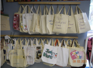 Image of canvas bag totes handing on hooks in a classroom